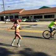 Female road runner with biker